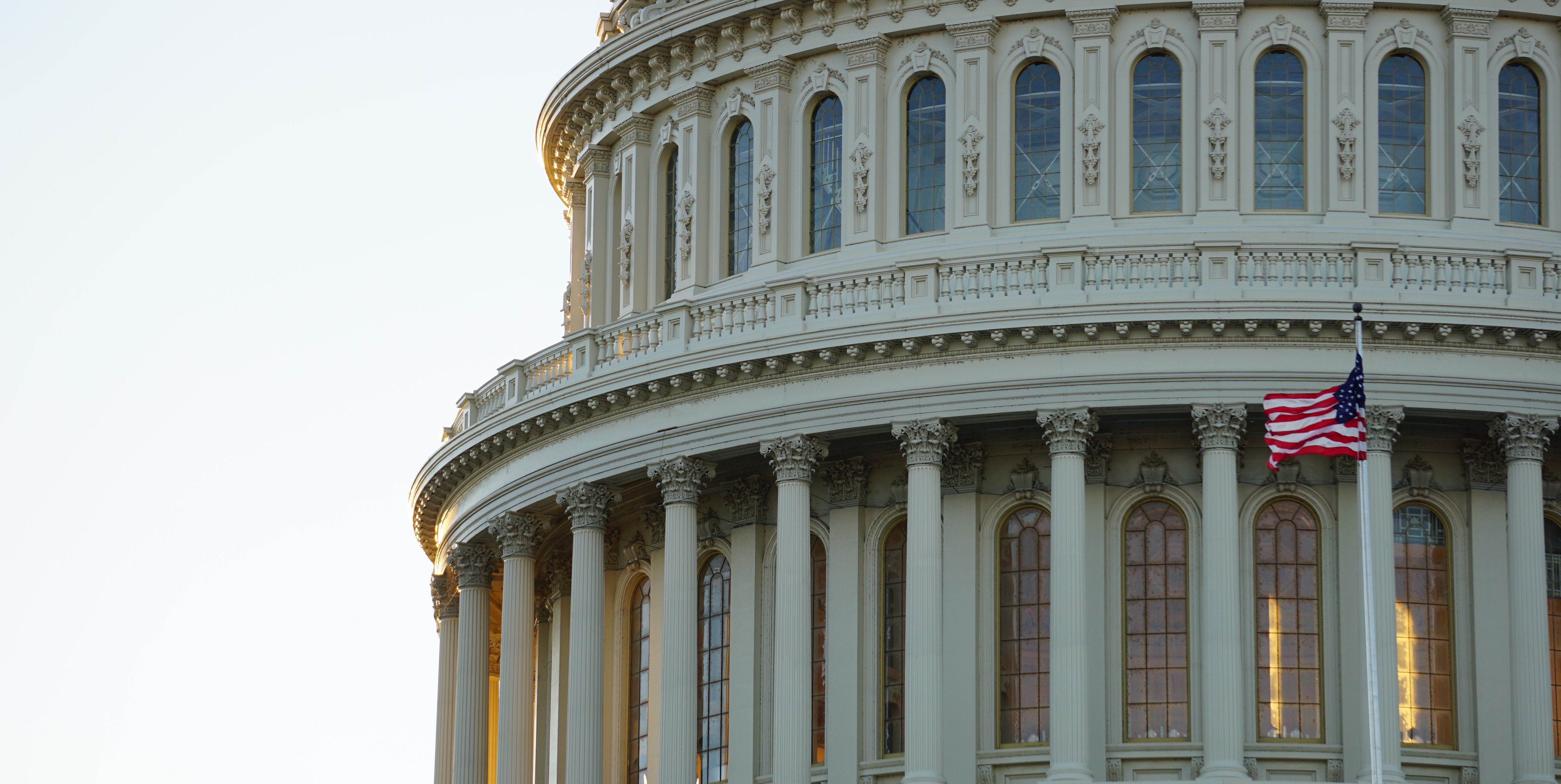 A close up section of the the U.S. Capitol building dome with a blue sky in the background.