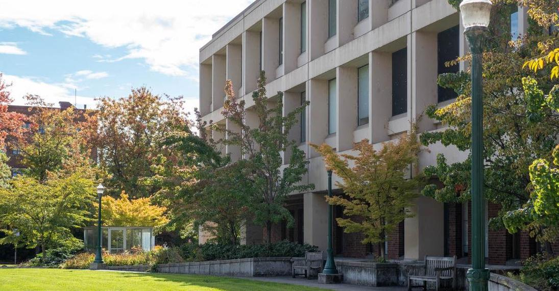Exterior of the building, Huestis Hall, and its courtyard, which includes light poles, wooden benches, green grass, and trees with leaves changing colors for the fall season.