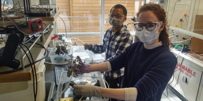 Doctoral students Lihaokun Chen (left) and Nicole Sagui assemble a bipolar membrane electrolyzer for testing.