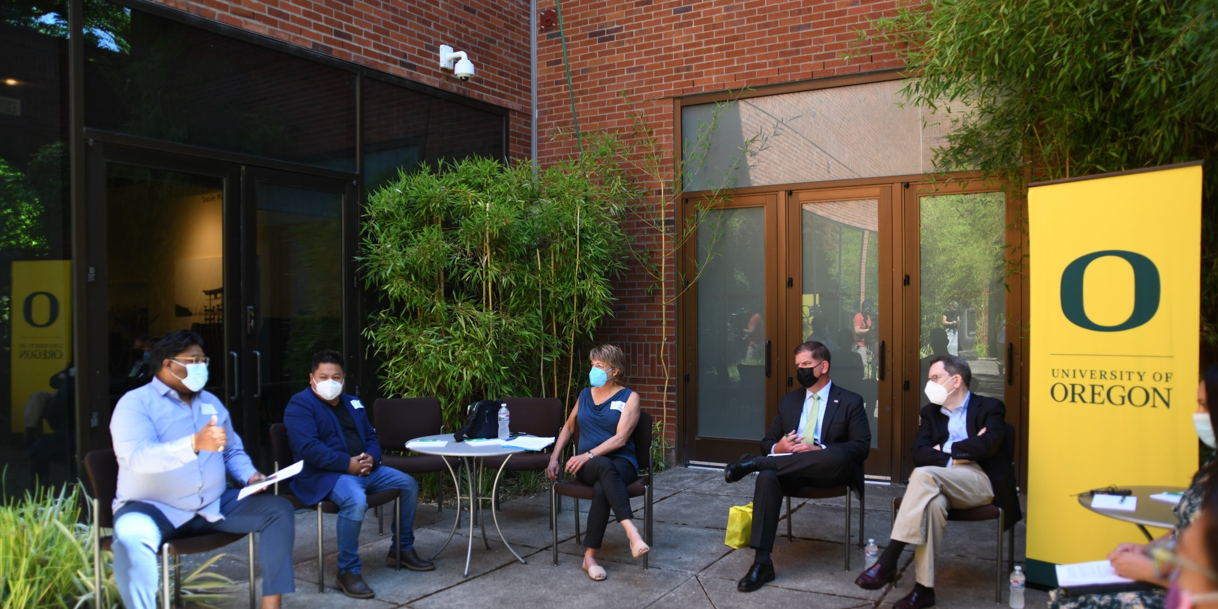 President Schill, Secretary Wash, and three others sit in a courtyard during a roundtable discussion.