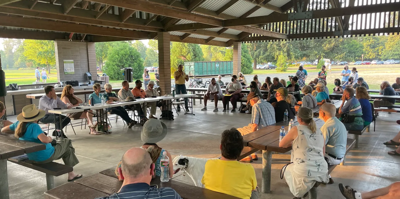 Community members gathered under a park gazebo for a town hall meeting.