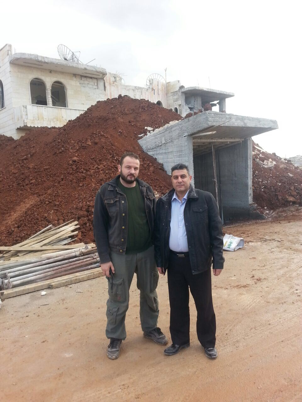 A picture of Dr. Dbais (left) with the late Dr. Al-Araj, (right) in front of emergency entrance to the hospital, which he covered with dirt to fortify the building