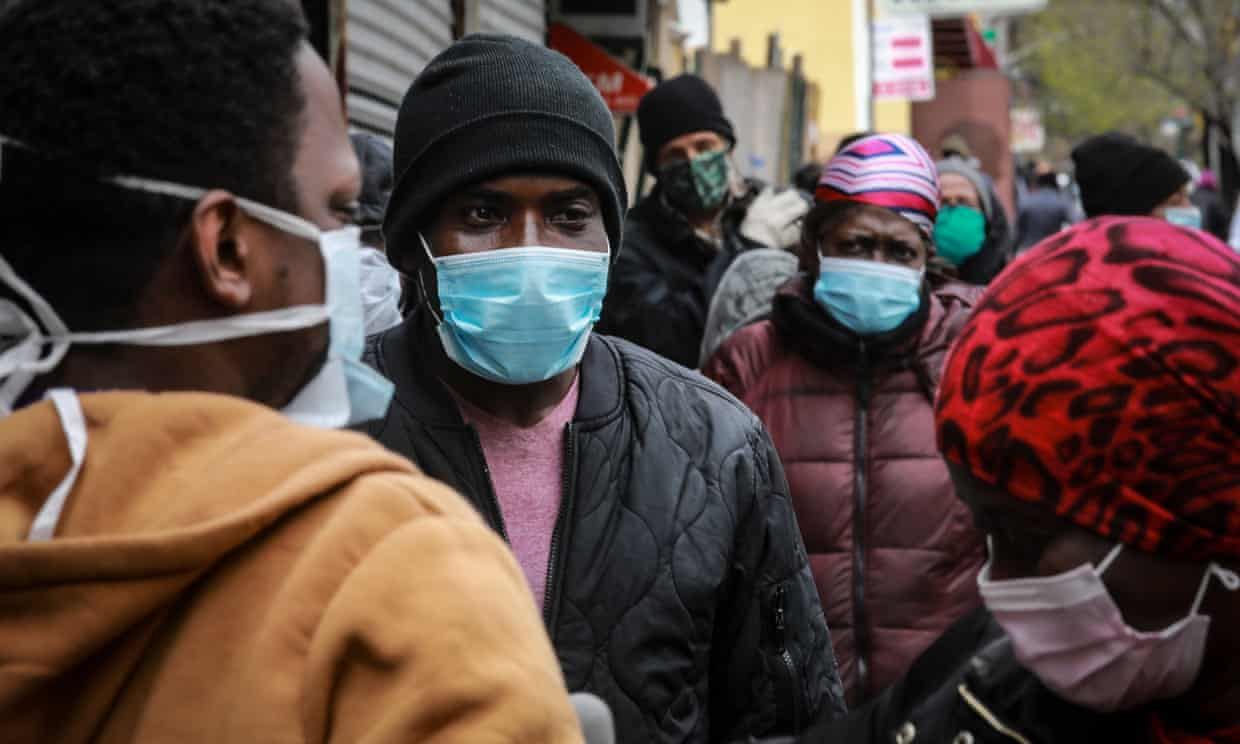 People wait for a distribution of masks and food in the Harlem neighborhood of New York City. Photograph: Bebeto Matthews/AP
