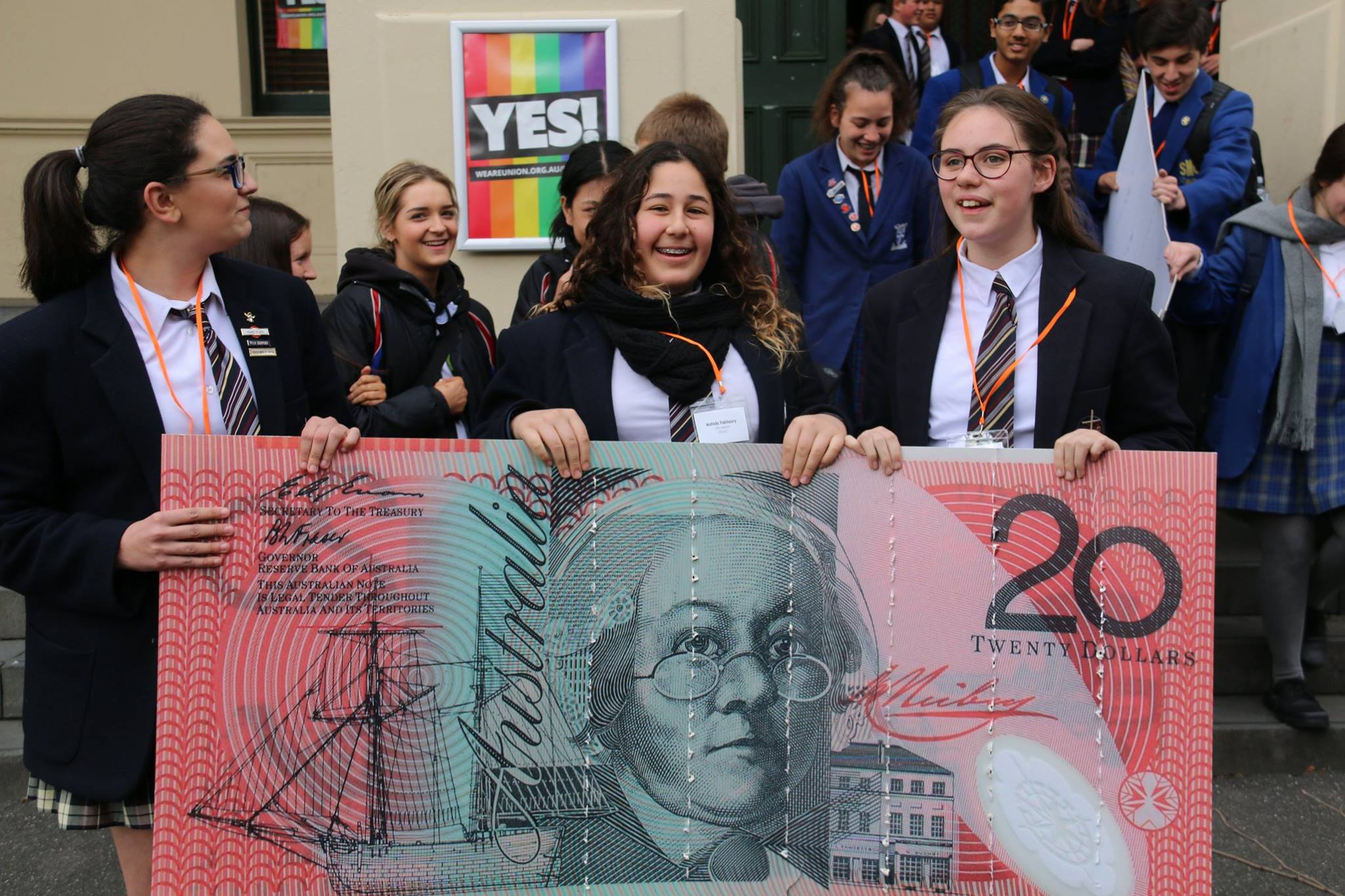 Three smiling high school students holding oversized image of $20 bill