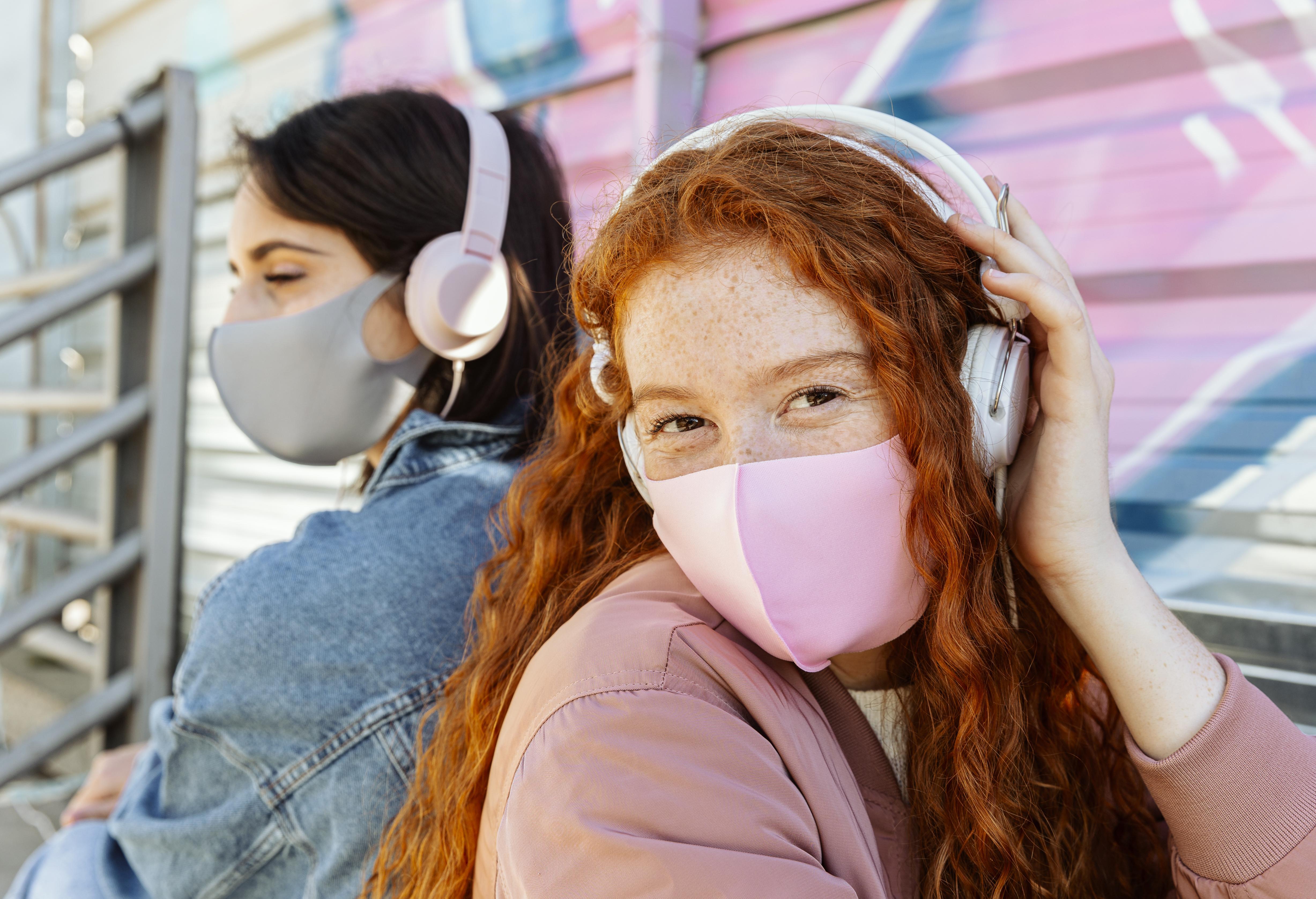 female-friends-with-face-masks-outdoors-listening-music-headphones.jpg