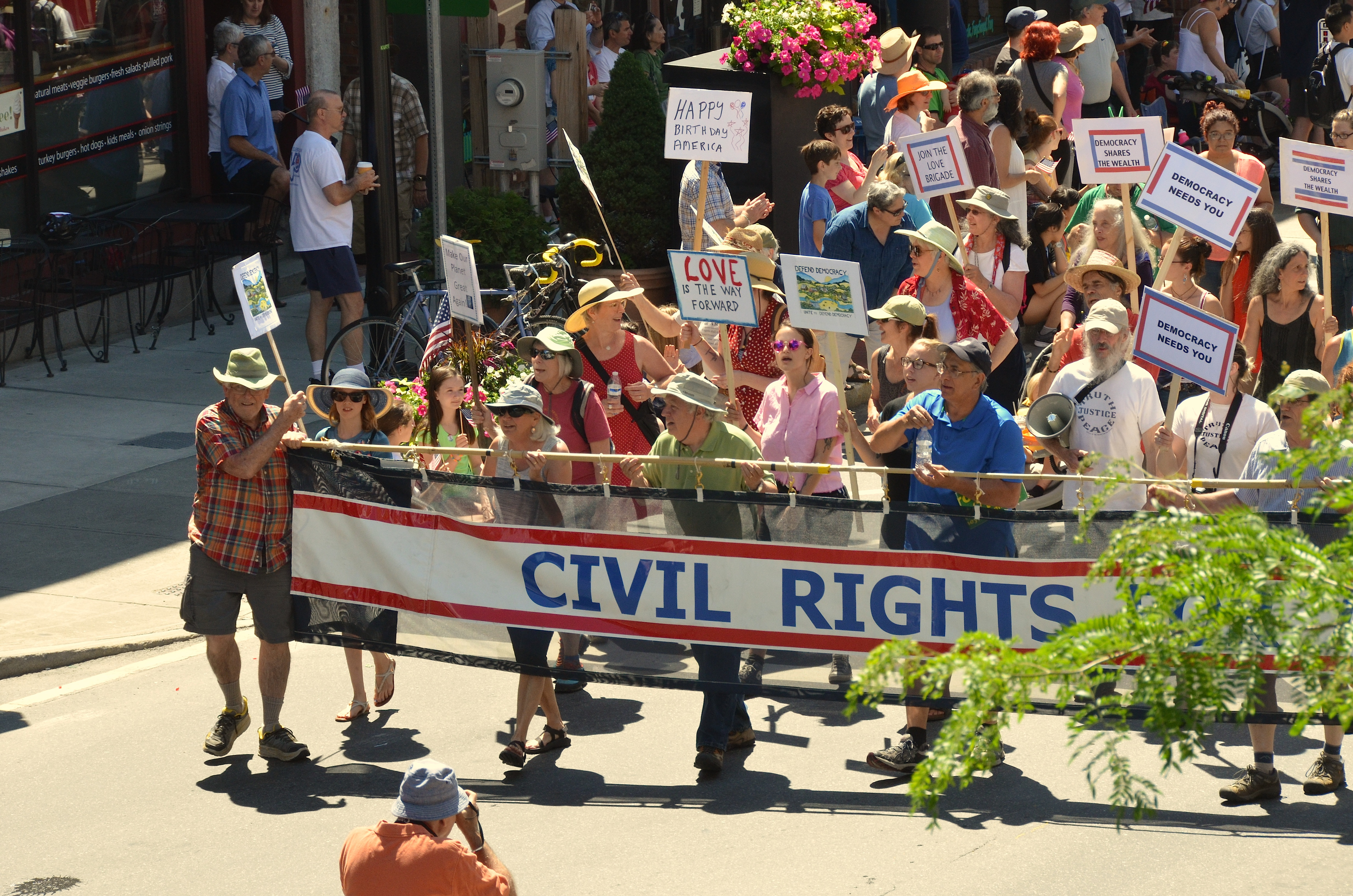civil rights banner being carried through brattleboro by engaged citizens