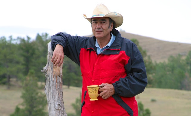 alex white plume standing in a red jacked beside fence