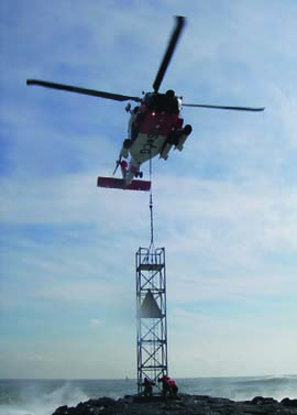 A Coast Guard MH-60 Jayhawk helicopter lowers a 25-foot, 2,540-pound tower to members of Coast Guard Aids to Navigation Team Cape May, N.J., for installation on the north jetty of Shark River Inlet. The previous tower was destroyed by Hurricane Sandy. U.S. Coast Guard Photo by Chief Warrant Officer Christopher Runt