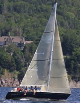 Sailing past Beinn Bhreagh, the former estate of Alexander Graham Bell on Baddeck Bay. © Jamie MacMullin