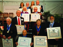 The 2013 NSHOF Inductees (from bottom, left to right): Stuart Walker, Runnie Colie, Timmy Larr, Richard Rosenfeld (accepting for grandfather Morris Rosenfeld) Steve Taylor (accepting for grandfather Starling Burgess) Julia Clough (accepting for grandfather John Alden), Frank Butler, Brooke Blackaller*, Dave Curtis, Lisa Blackaller*, Bill Buchan (*accepting for their father Tom Blackaller) © NSHOF/Jack Hardway