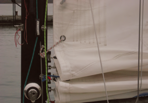 These two images show the tack end of a double, single line reefing system where the tack and the clew have its own dedicated line. Reefing in this case is done from the cockpit.
