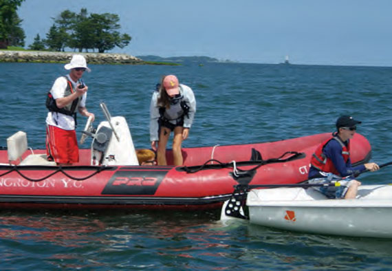 "Noroton YC instructor Connor Brady notified the club's Junior Sailing Office of an on-the-water ""emergency,"" while instructor Laura Cuccio tended to ""injured"" skipper Will Crane. Calvin Crosby (at right) sailed the 420 to shore"