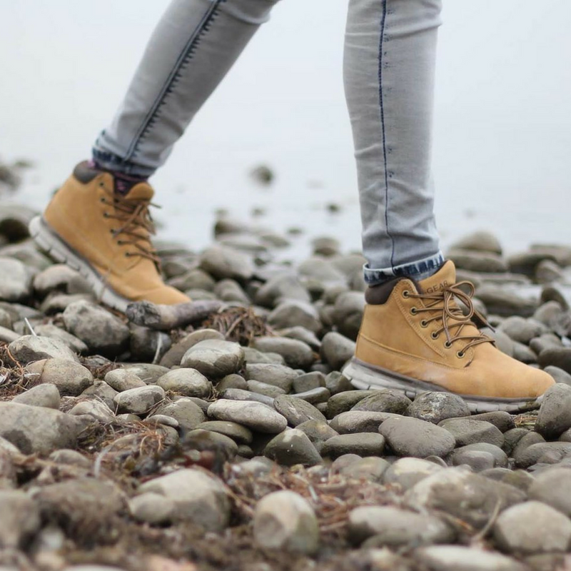 Women walking on stones on the water's edge