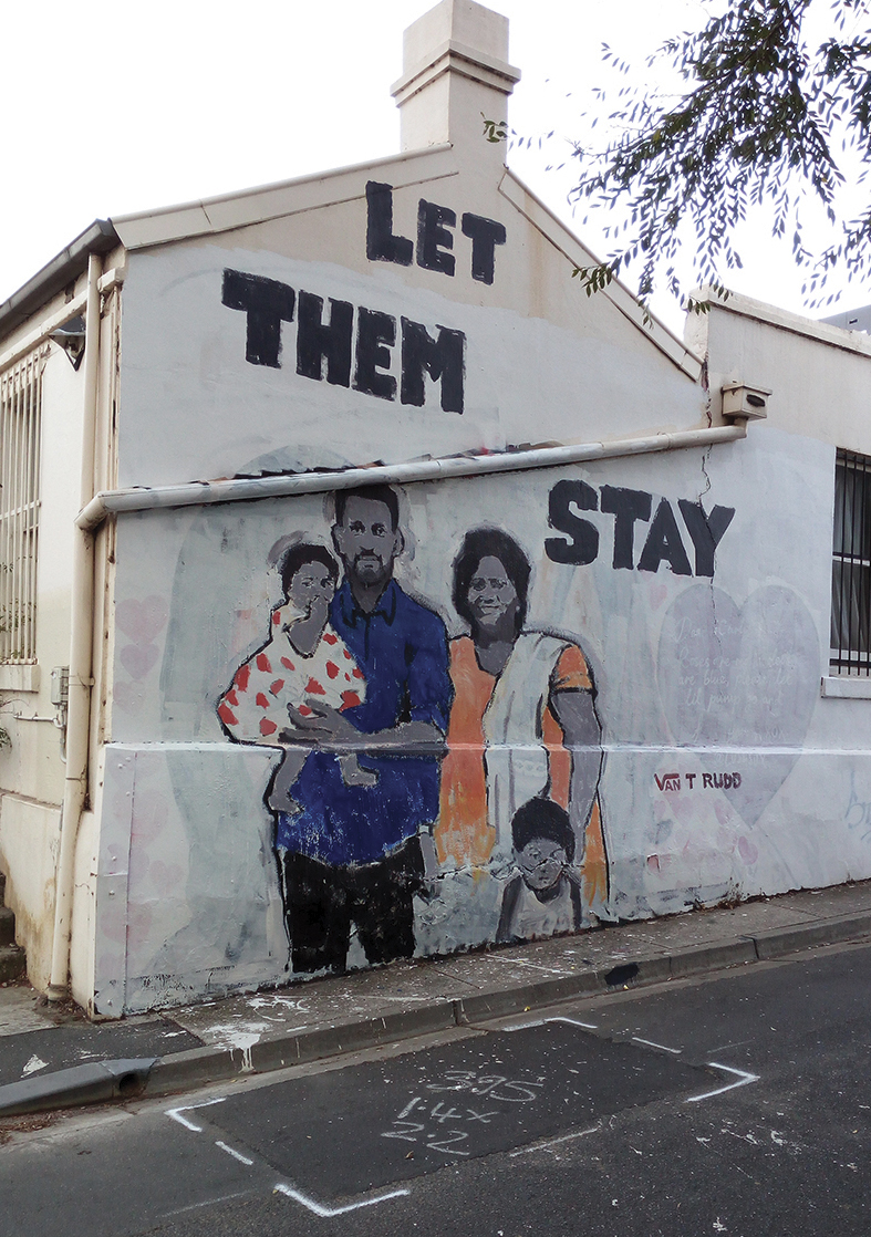 Graffiti of the Murugappan family on the side of a house with the words 'let them stay'.