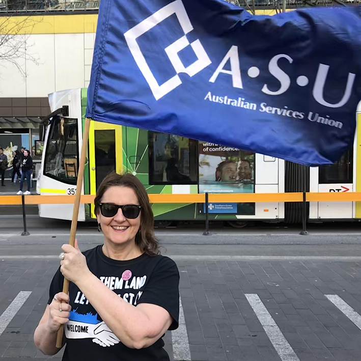 Fran Mckechnie smiling and waving an Australian Services Union flag