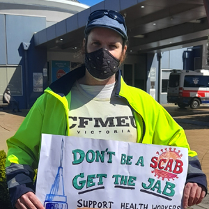 """Zane Alcorn holding a sign that says """"Don't scab, get the vax"""""""