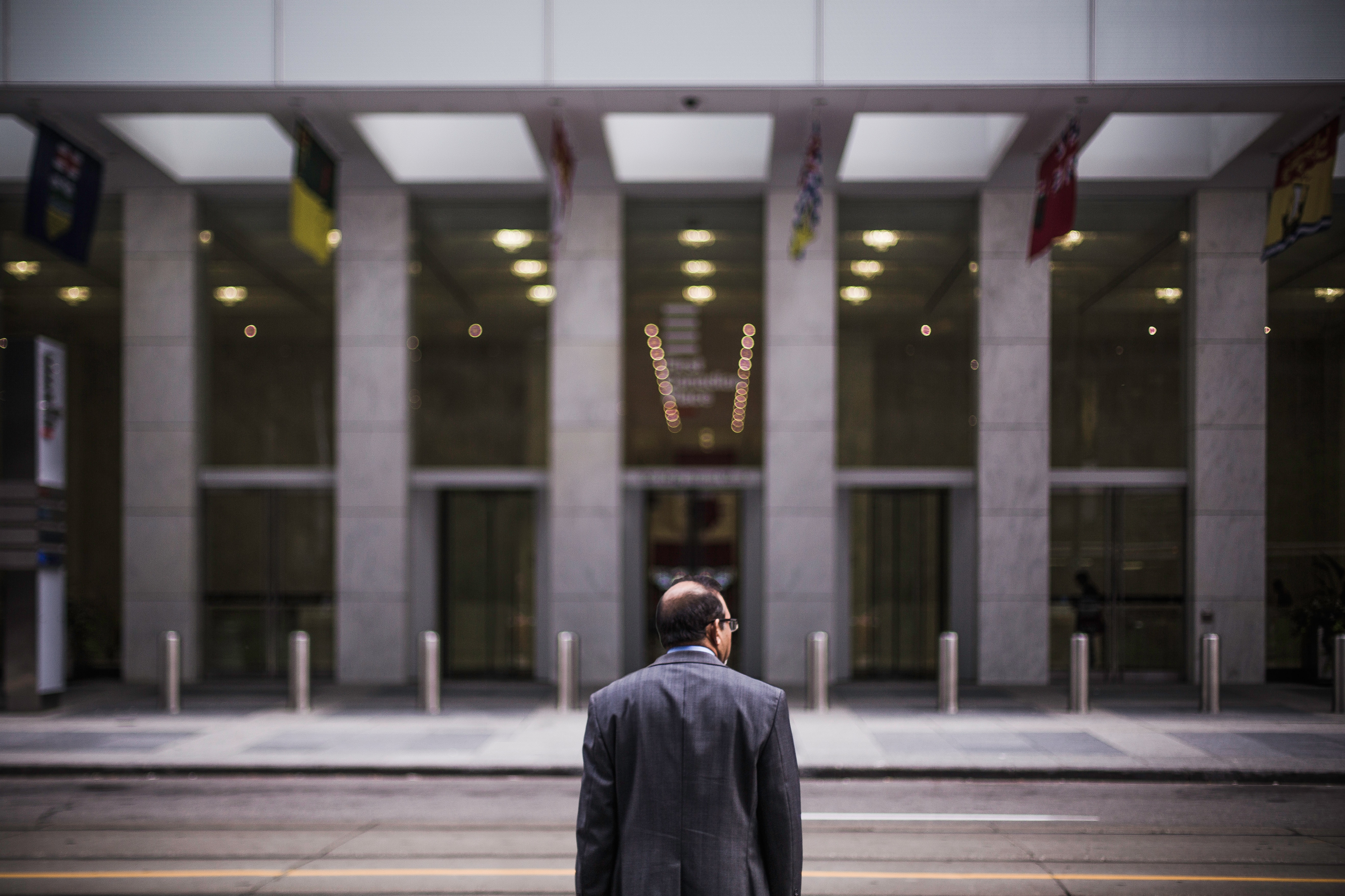 Middle-aged man stands facing away from camera toward the front of a financial/government building