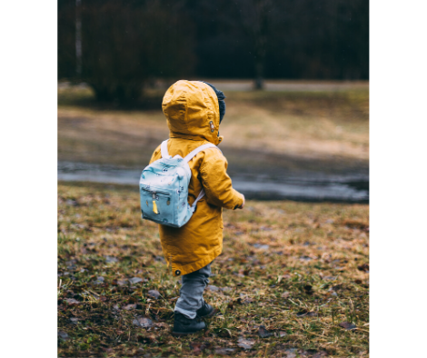 small child in yellow rain coat wearing a blue back waits on grass by the side of a country road. Source Daiga Ellaby via Unsplash