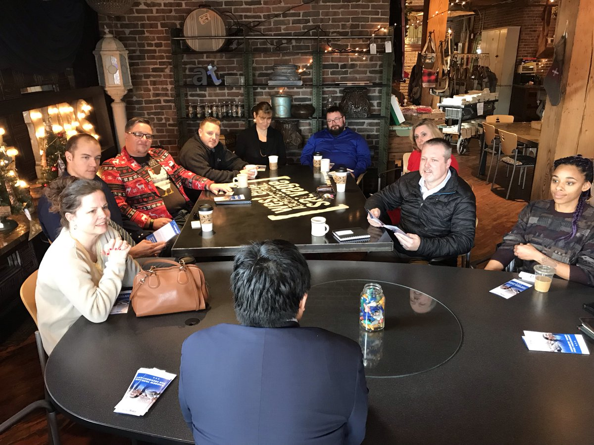 Andrew Yang sitting at the head of a table with local business owners listening to his ideas