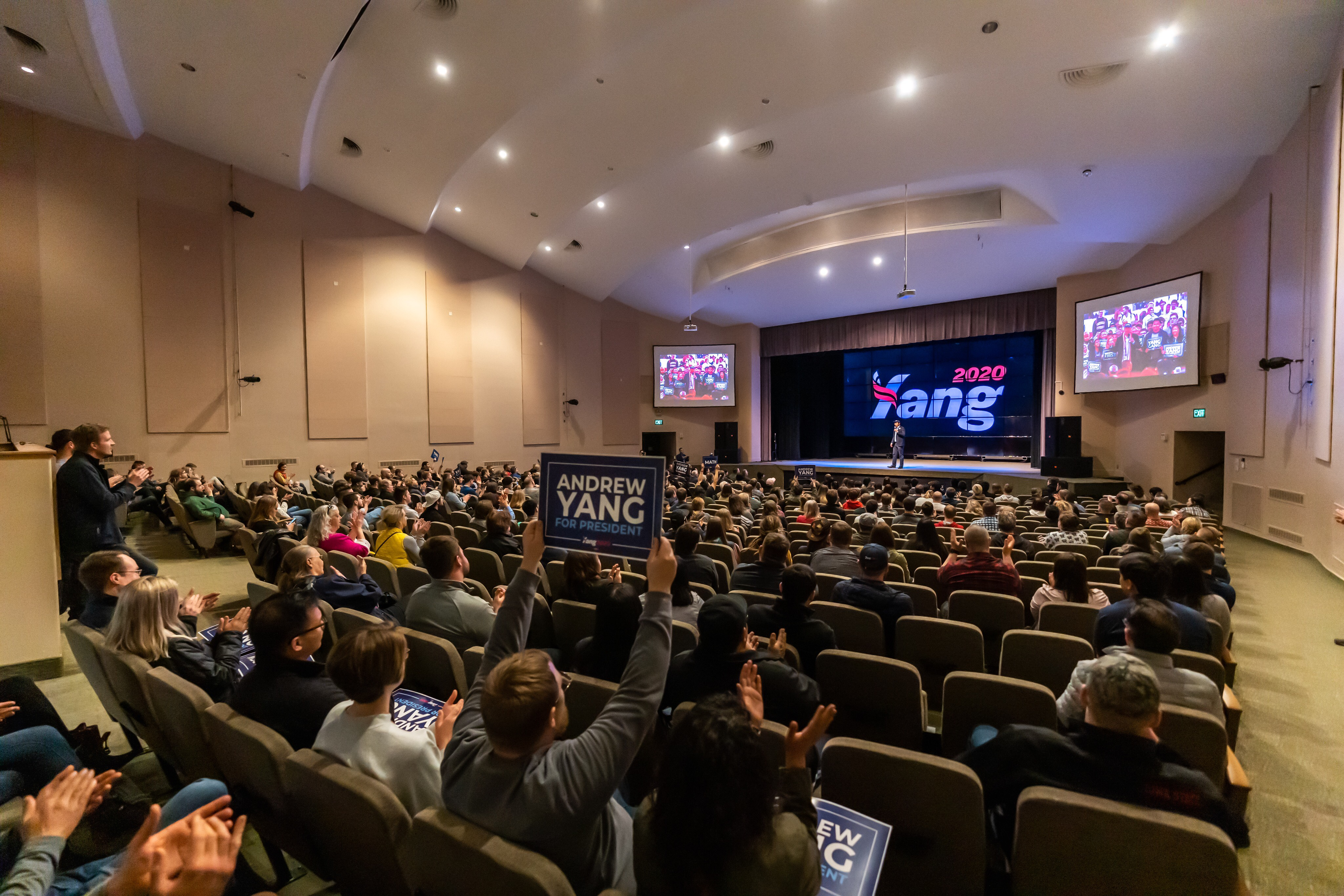An auditorium filled with Iowans listening to Andrew Yang describe his vision for the future of America