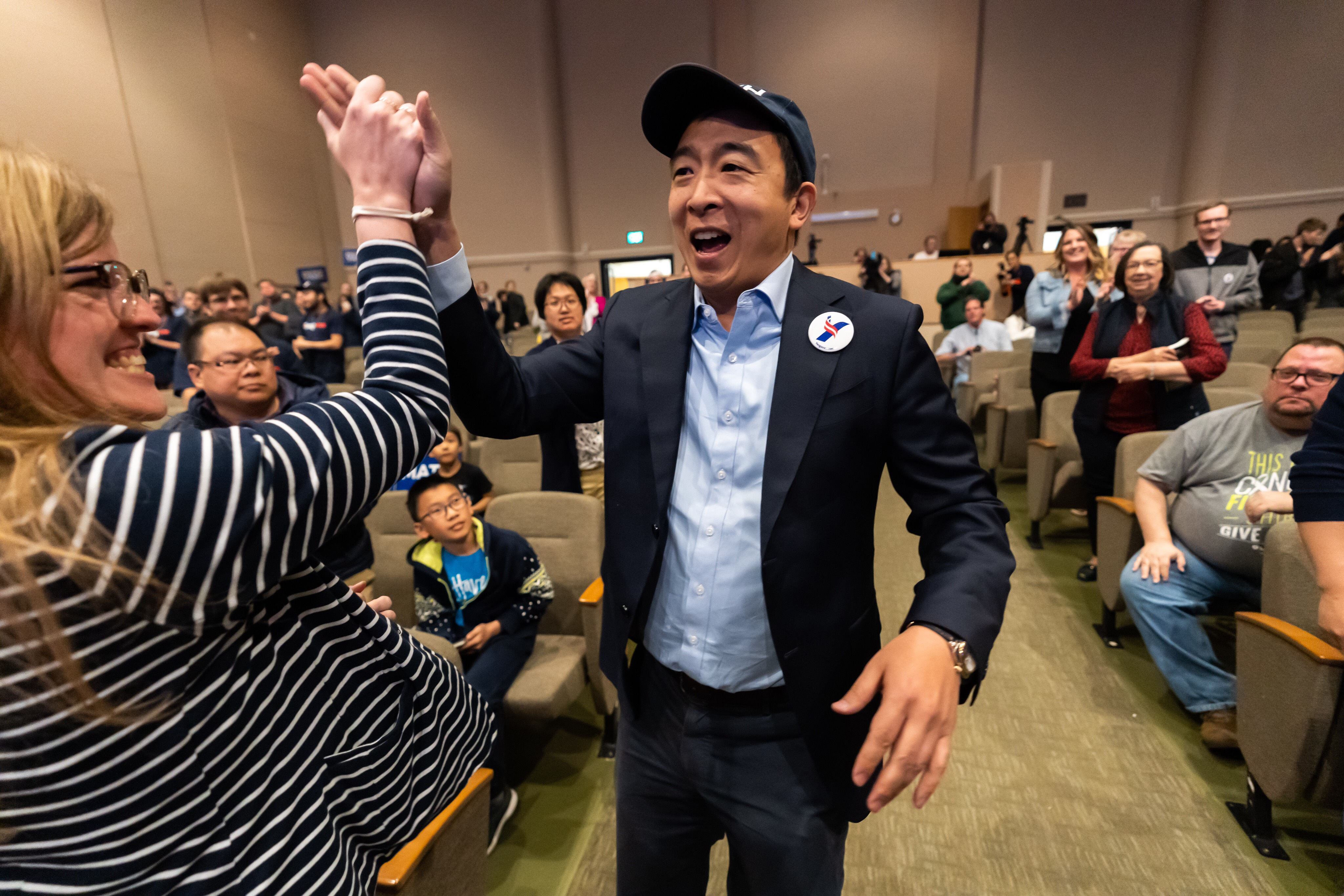 Andrew Yang high fives a supporter after his Iowa Town Hall
