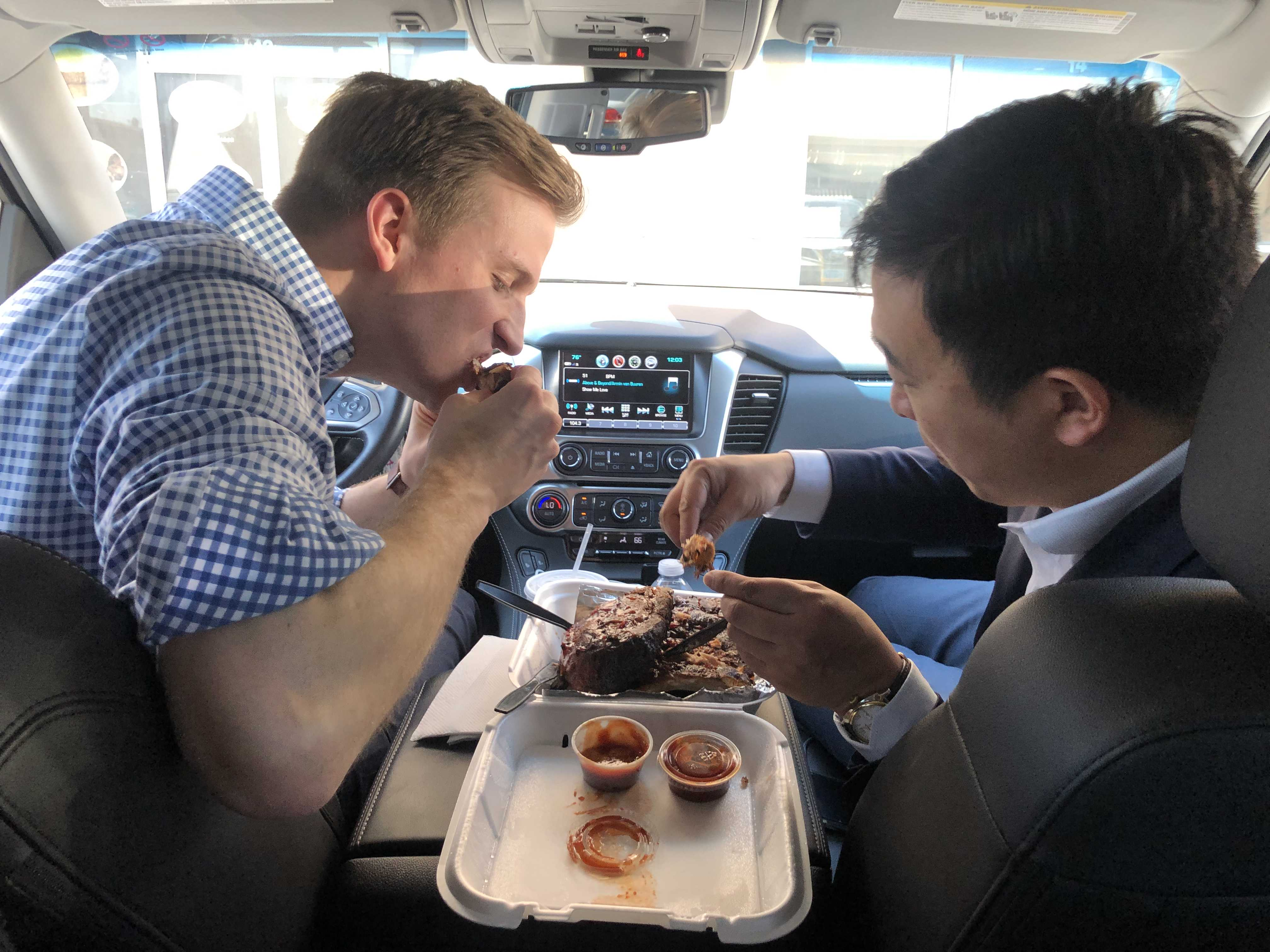 Zach sits in the driver's seat eating food with Andrew