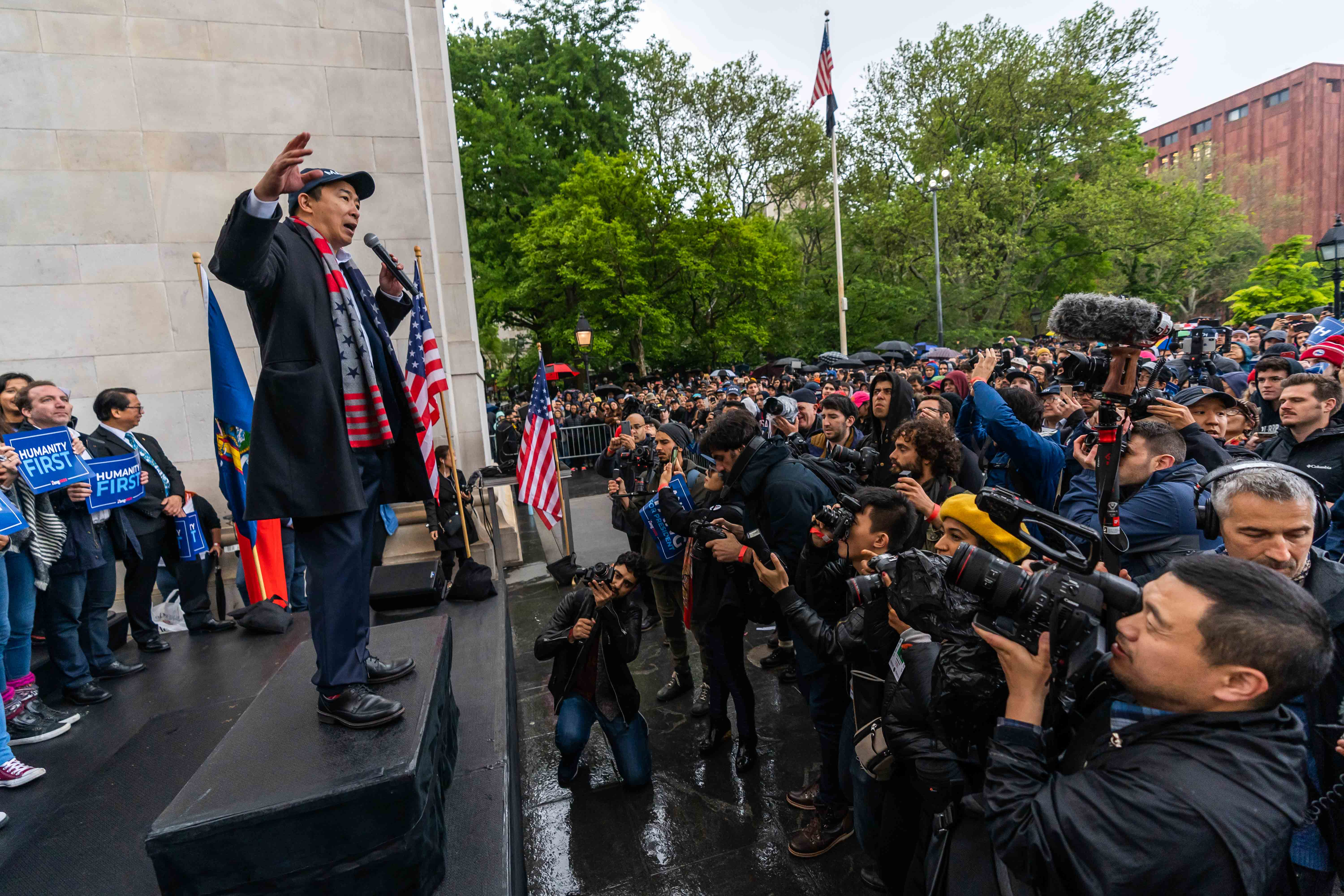 Andrew Yang stands in front of a crowd in Washington Square Park, delivering a speech as the rain falls