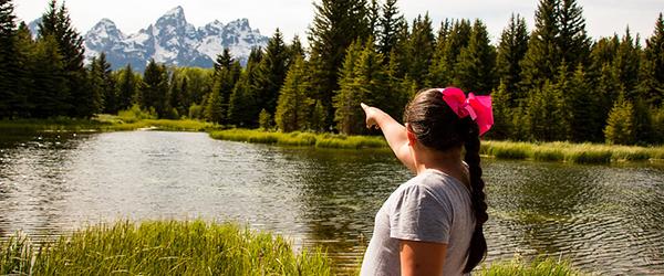 Girl points at Teton range