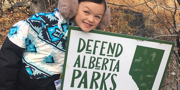 A child wearing winter clothing is smiling and leaning over a lawn sign that says 'Defend Alberta Parks'