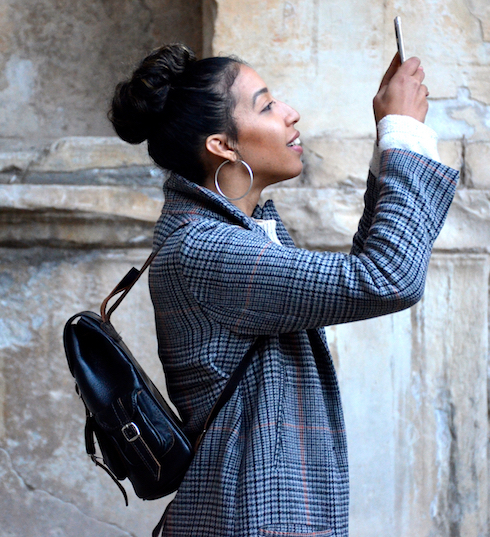 Woman looking at smart phone held above her head