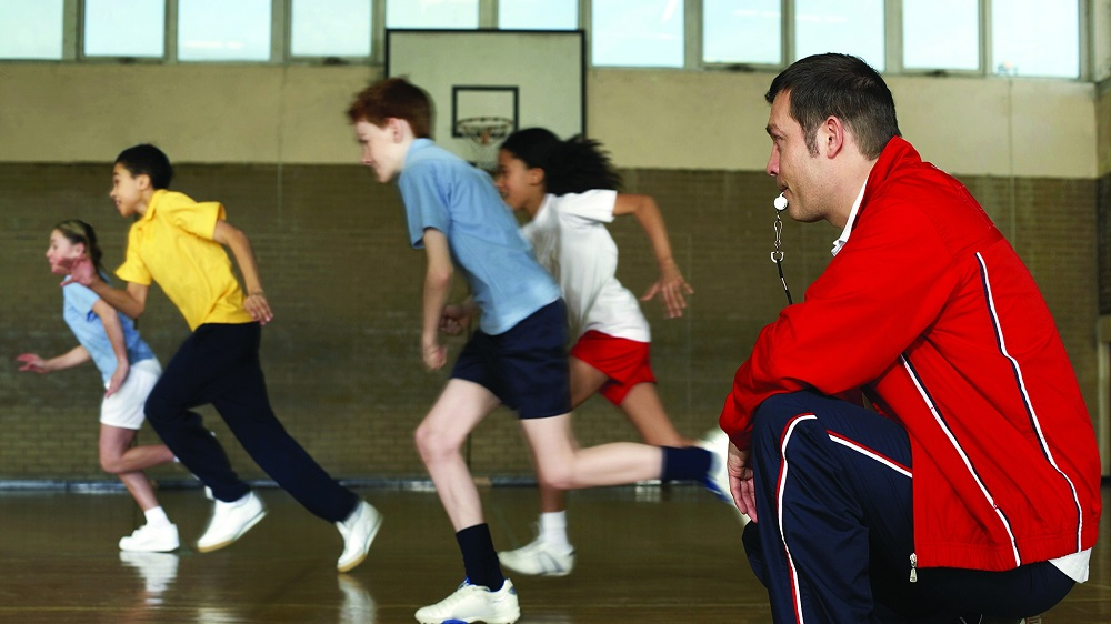 coach and kids running in gym
