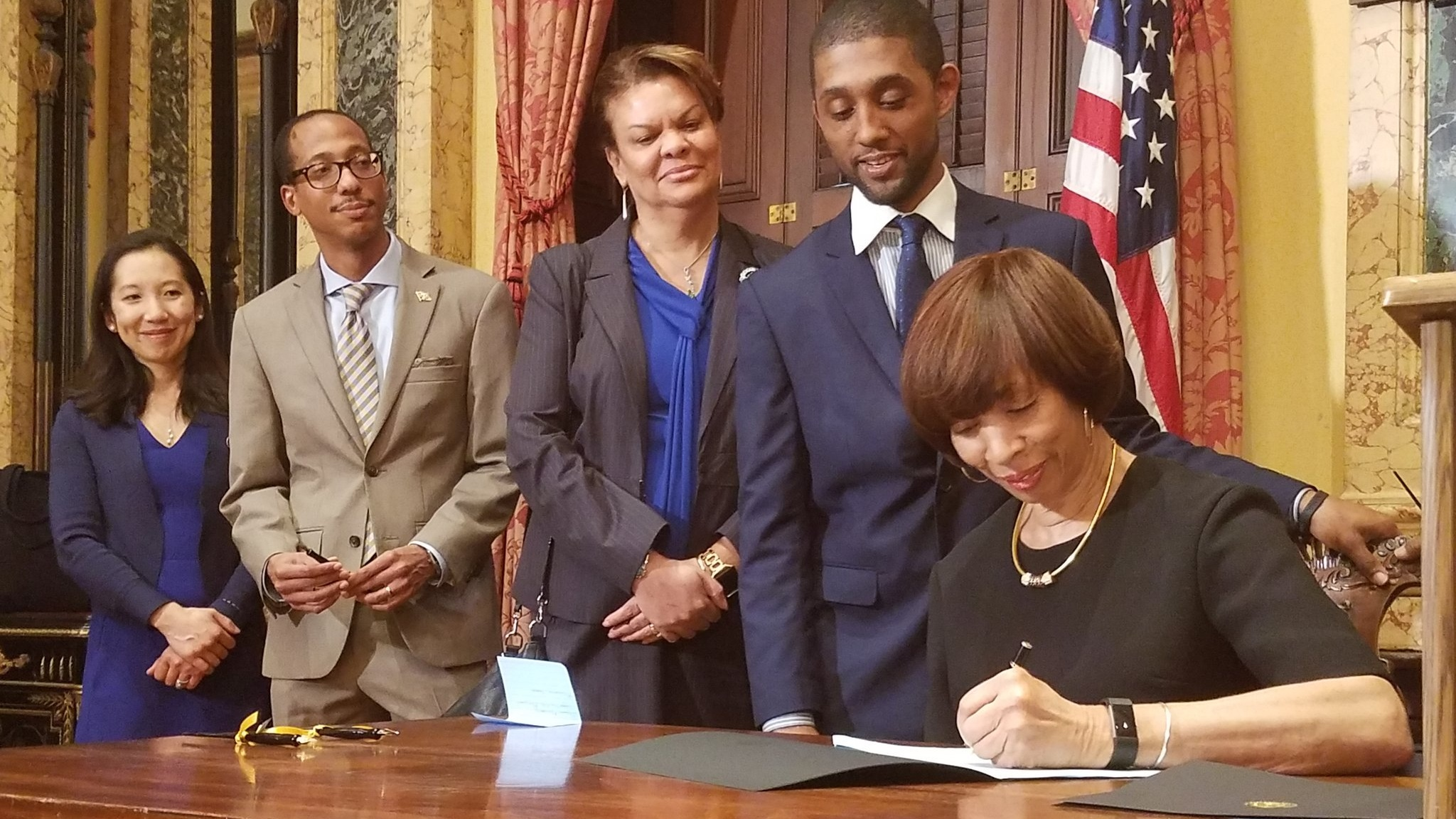 Baltimore City Mayor Catherine Pugh signs the Kids' Meal Bill as the Health Commissioner and Council Members look on.
