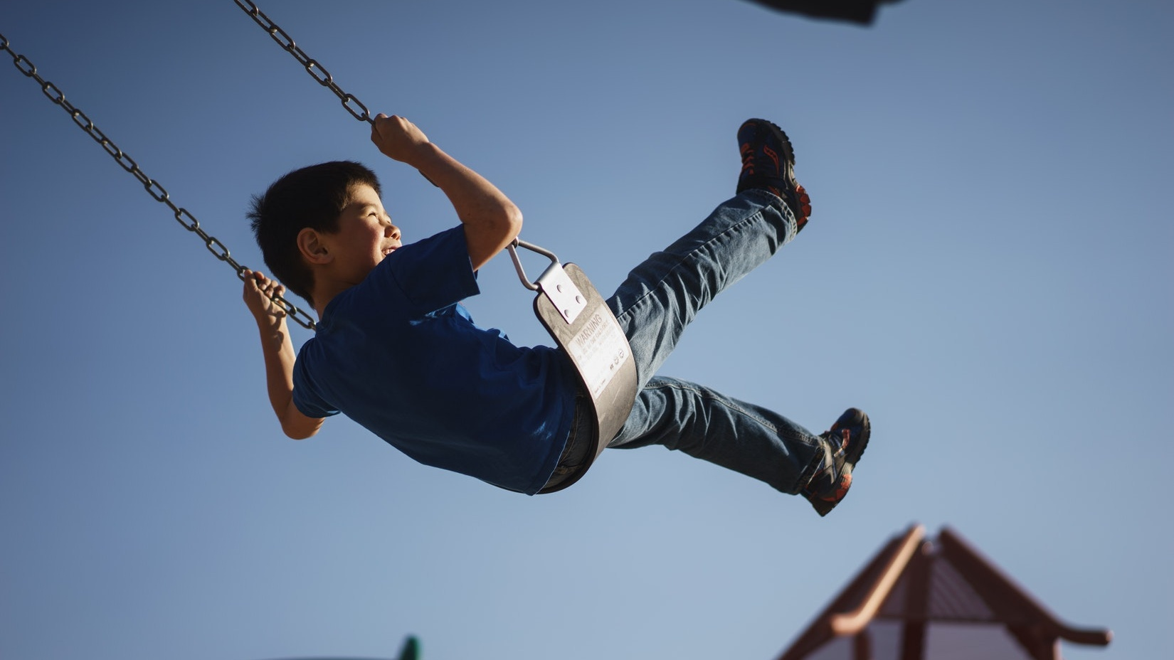 Child on swing in playground