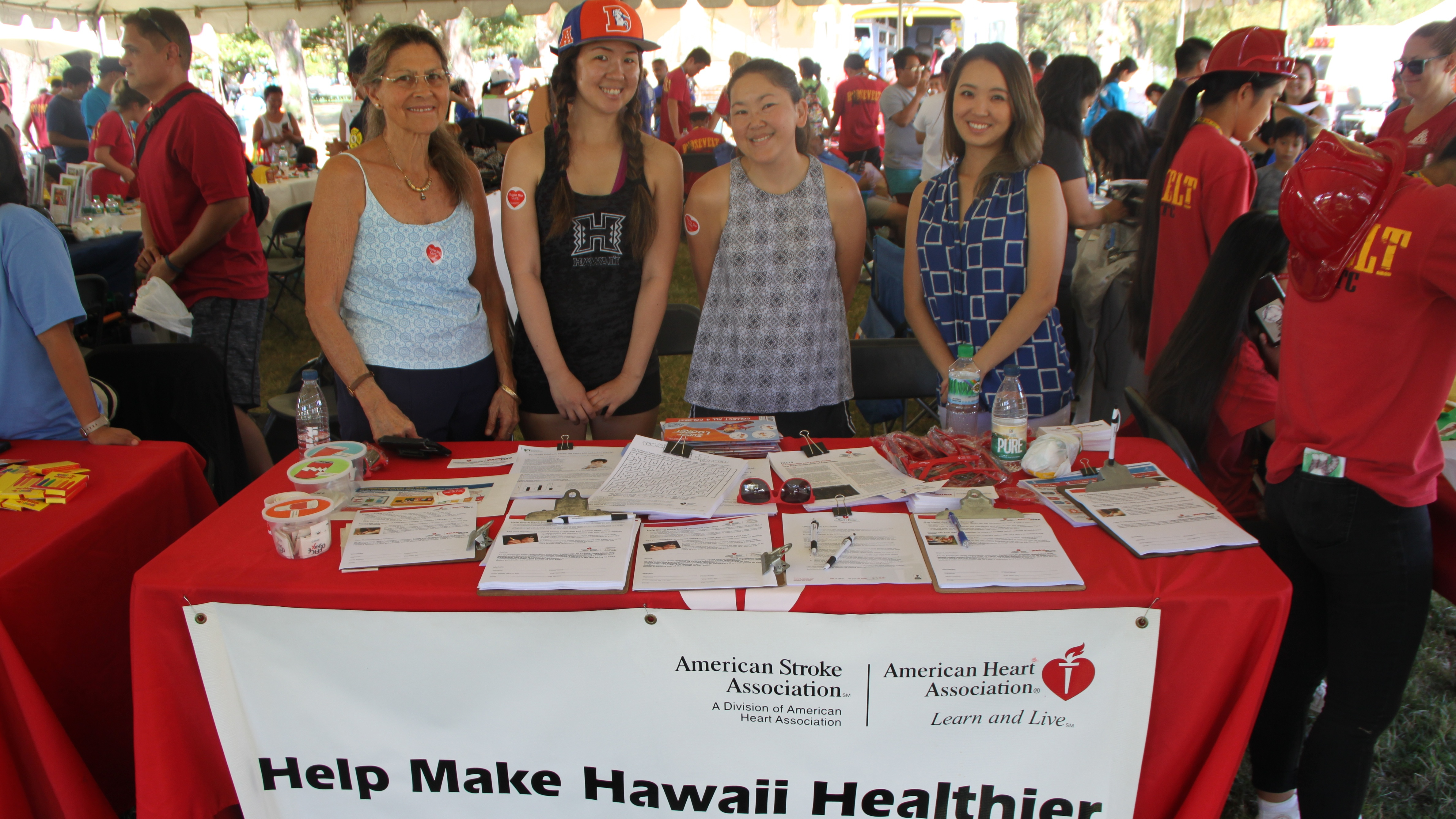 4 women standing at a recruitment table
