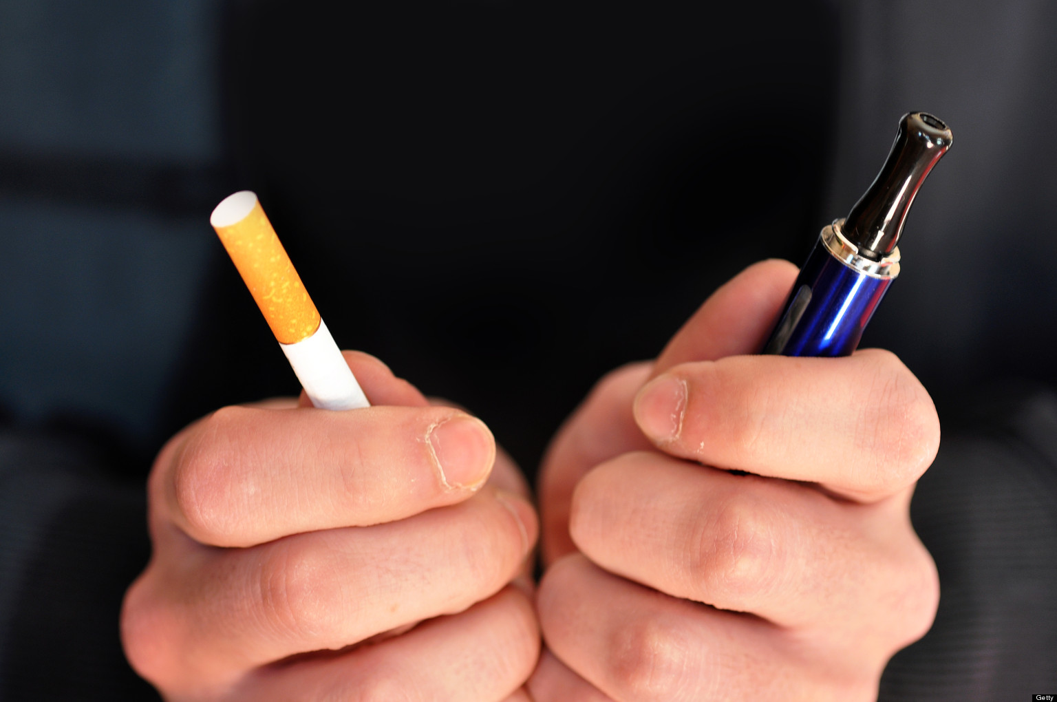 A picture of two hands one holding a cigarette and one holding an e-cigarette