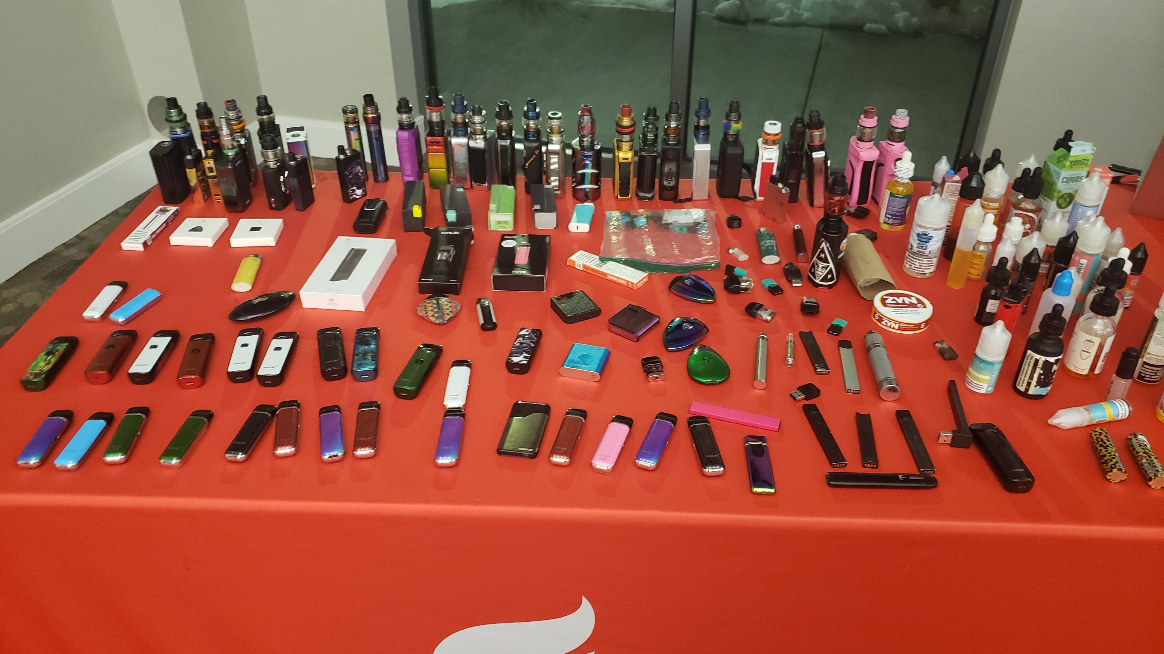 A table with a number of e-cigarette devices laid out to look at.