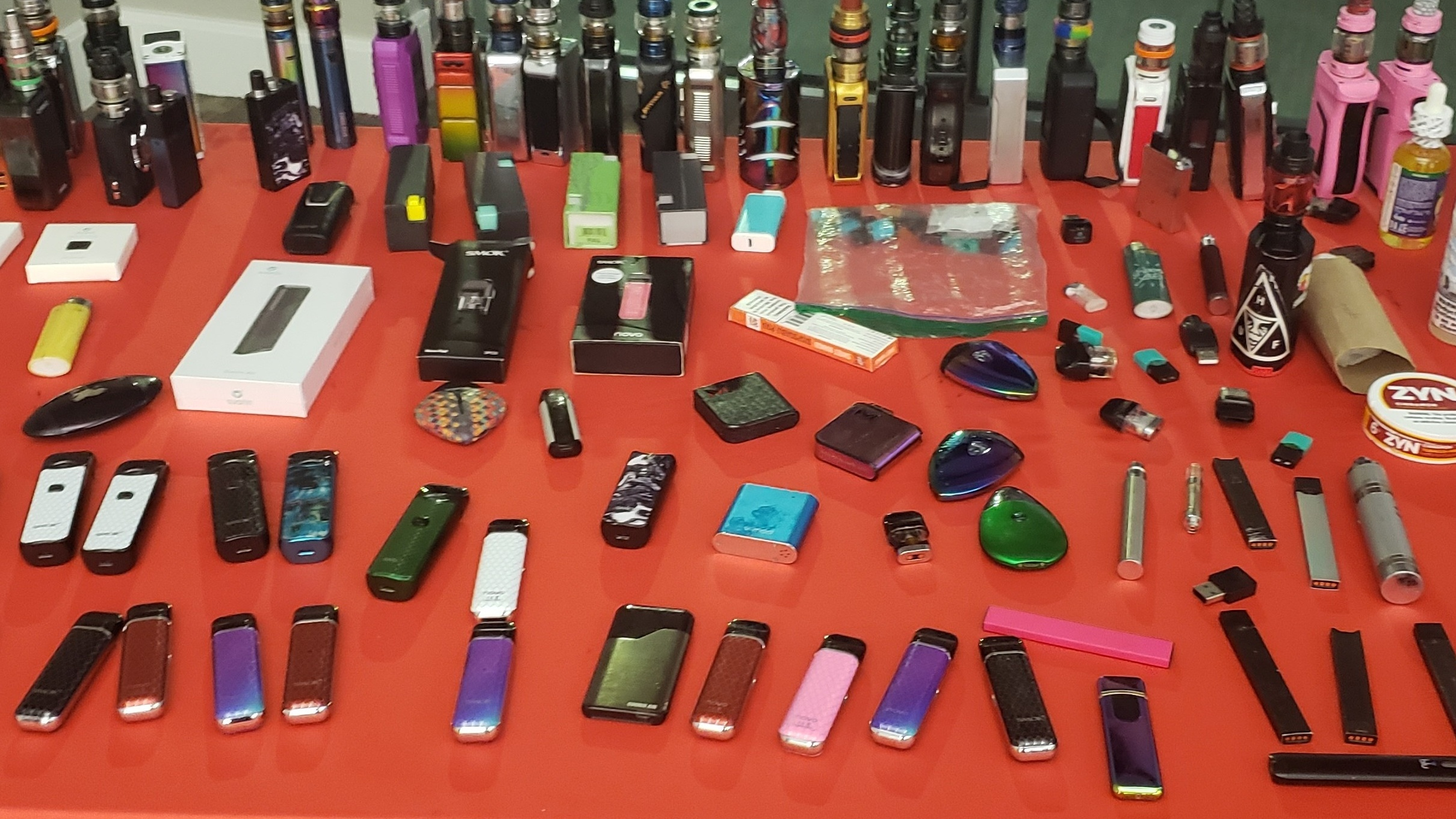 A table with a variety of vape devices confiscated from high school students