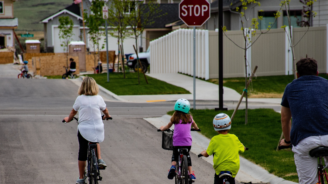 3 kids on bikes with an adult on a bike