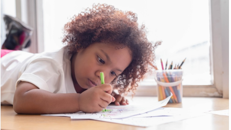 A little kid drawing on a piece of paper
