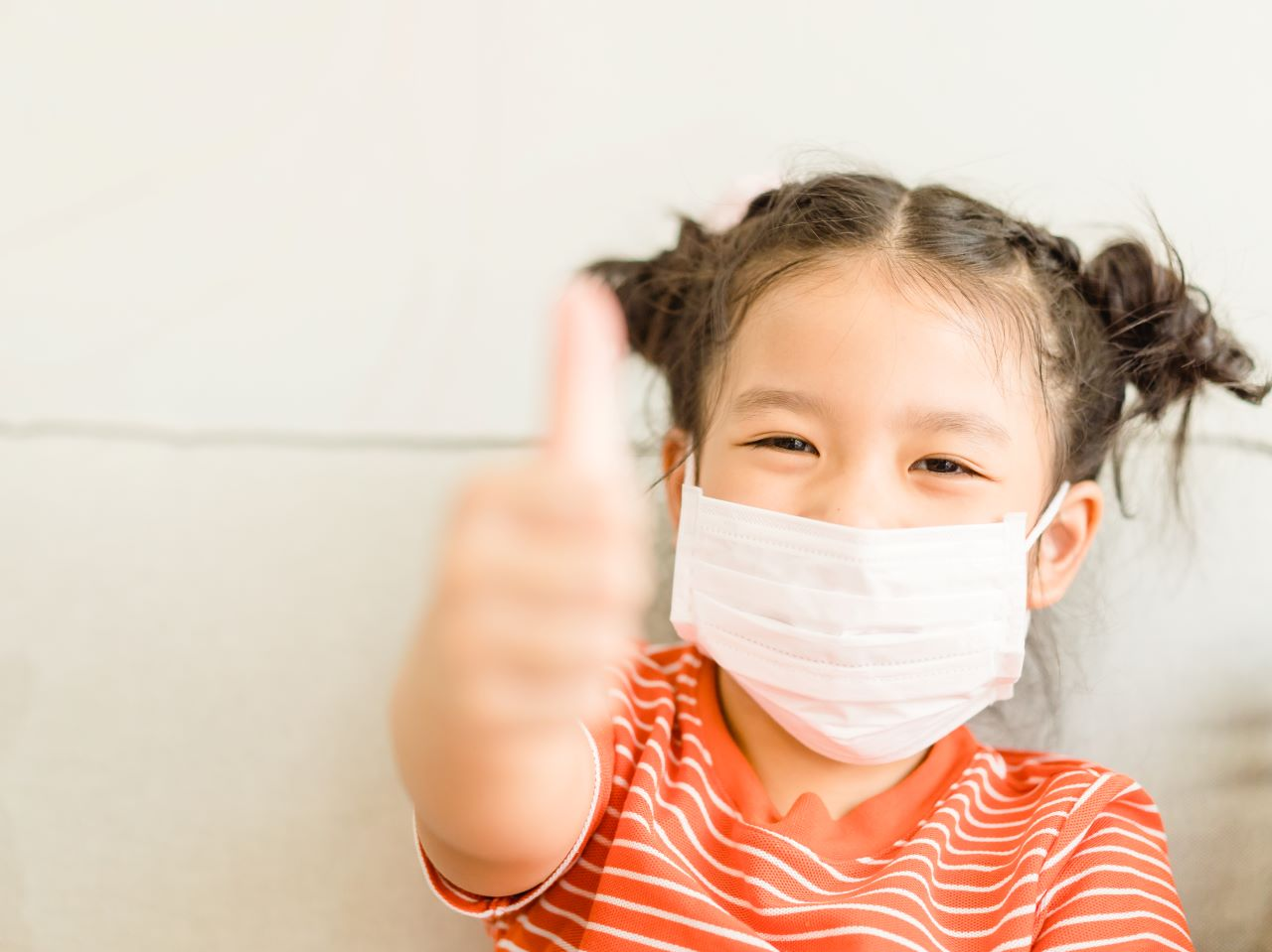 Little girl wearing a mask giving a thumbs up