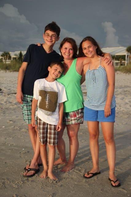 Ginnie on the beach with her three children
