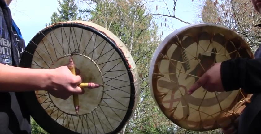 This picture shows the underside of two drums, held by Indigenous youth. The picture was taken from below, looking up to the sky and trees.