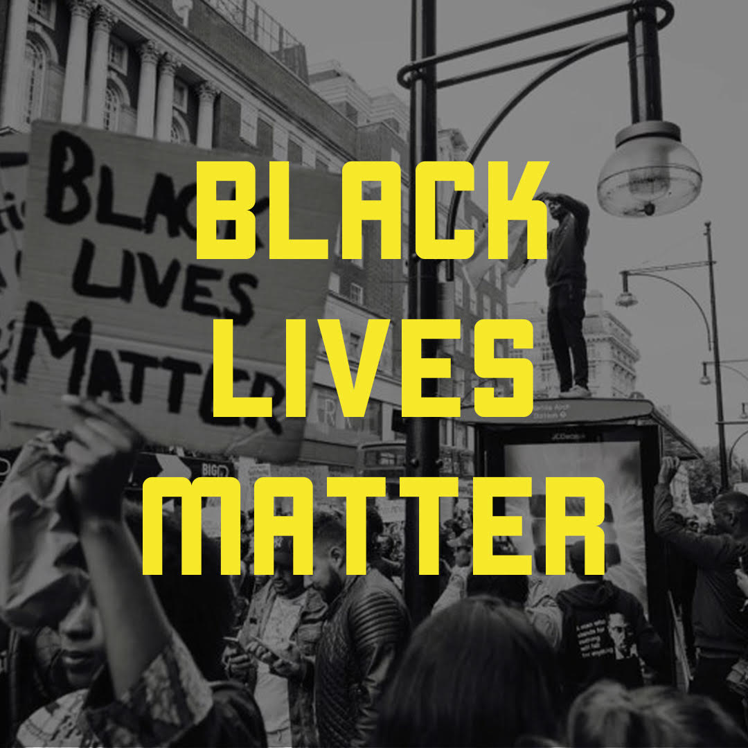 "Yellow text in capital letters that reads ""Black Lives Matter"". Behind the text is a black and white image of a Black Lives Matter protest on a street."