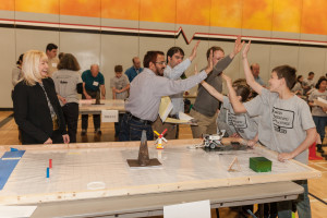 A team in the First Annual Lego Robotics Challenge gets hi-fives from the judges