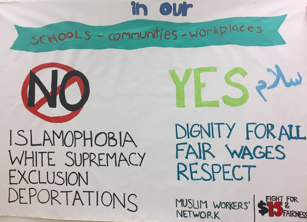 "A hand-painted banner of the Muslim Workers' Network and the Fight for $15 & Fairness campaign that reads, ""No Islamophobia, white supremacy, exclusion, deportations. Yes to dignity, fair wages, respect"