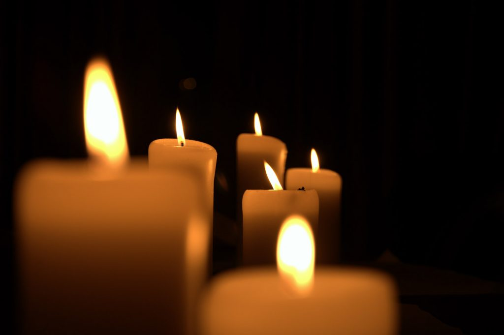 An image of candles lit against a dark backdrop during a vigil