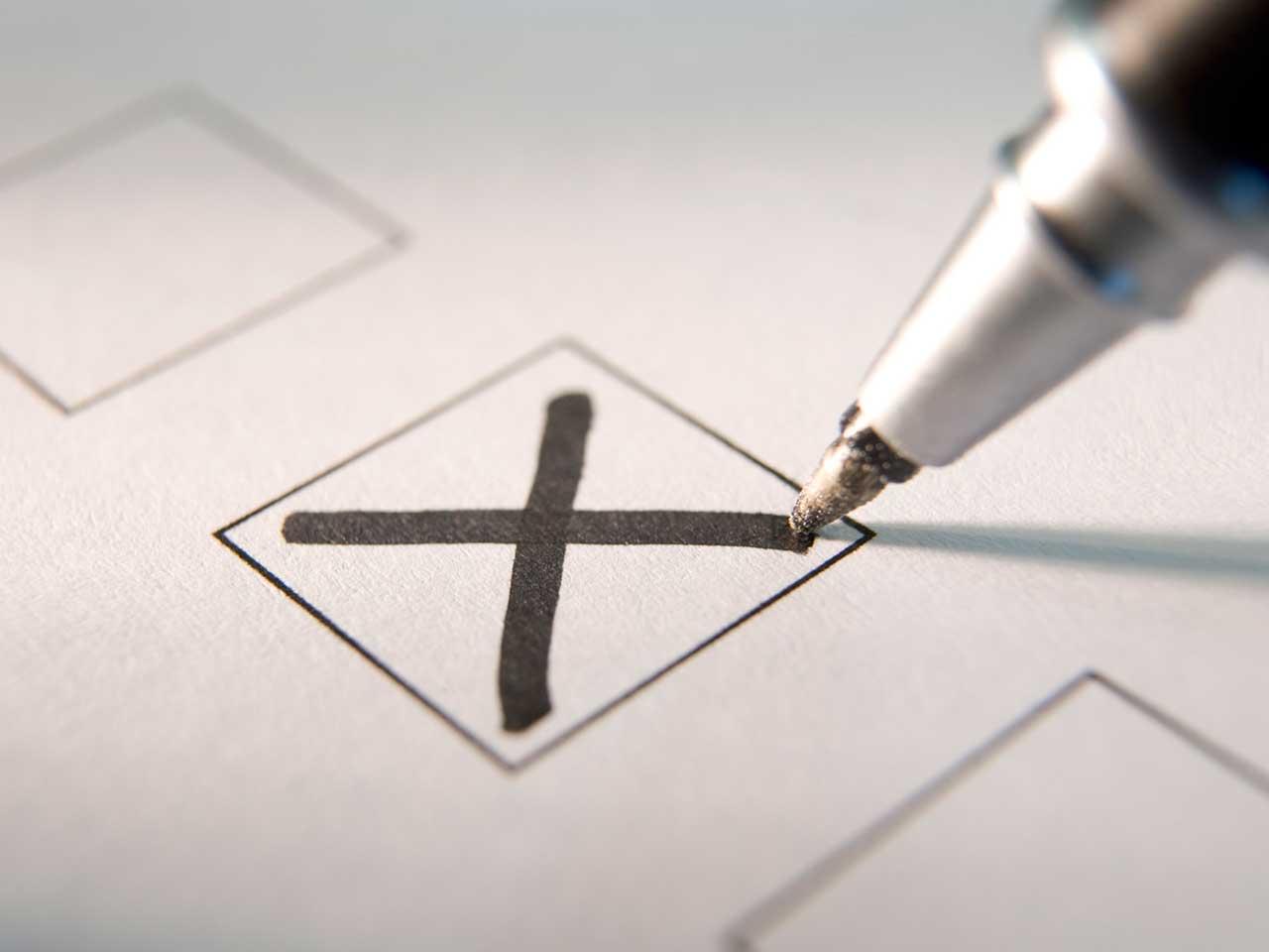 """An image of a pen marking an """"X"""" on a ballot paper"""