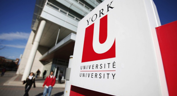 """A sign that reads """"York University"""" in the foreground and two students walking toward it in the background"""