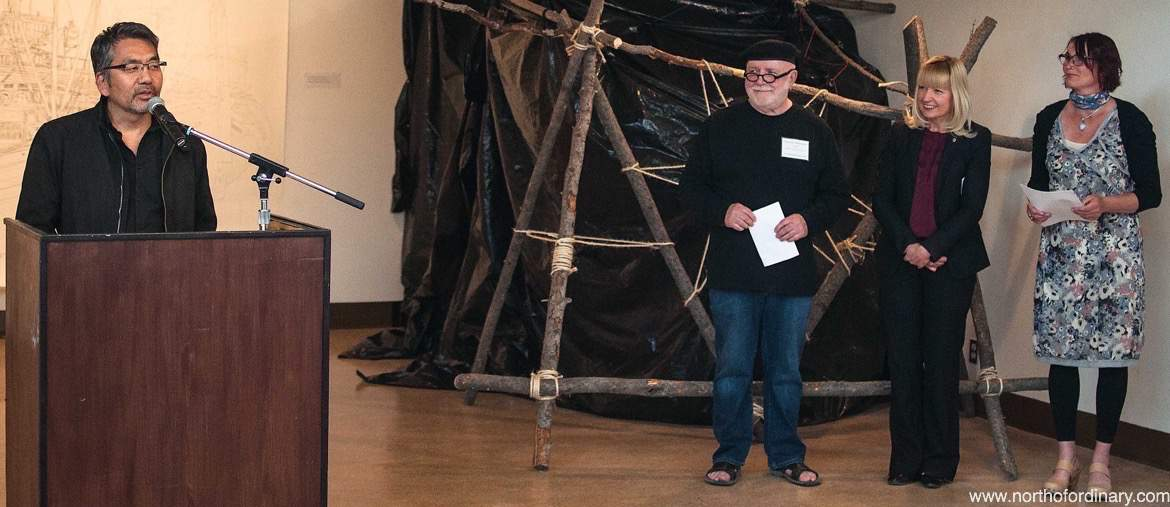 Jib Kobyashi gives as a speech as Harreson Tanner and Eileen Taylor look on